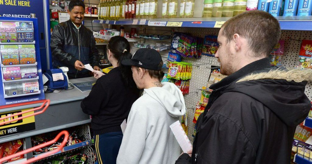 Punters buying lottery tickets at a shop with previous winners