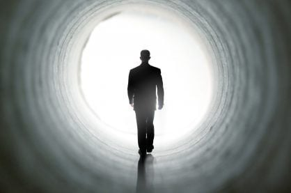 An image of someone walking towards the light after death