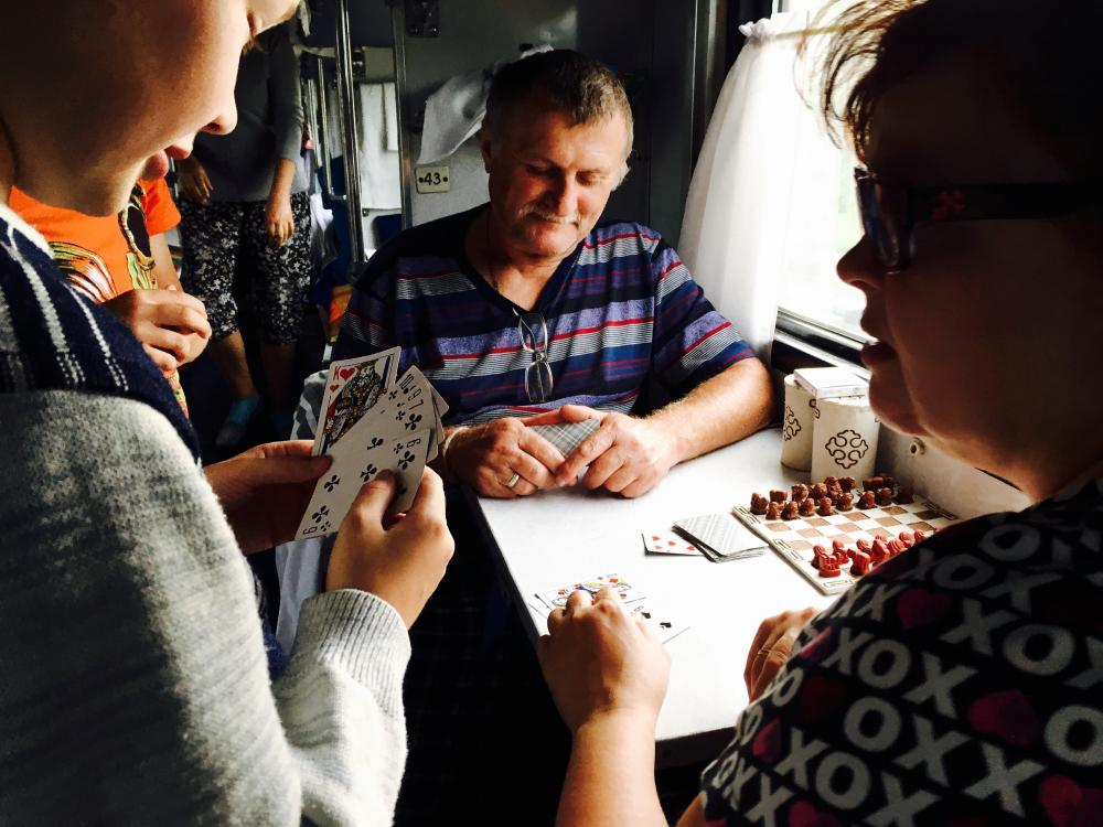 An image of three people playing Durak on a train