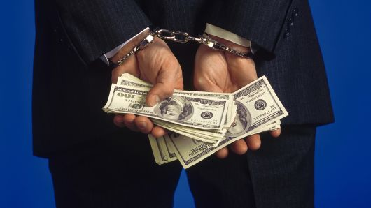 Someone handcuffed holding cash, representing the link between gambling and crime
