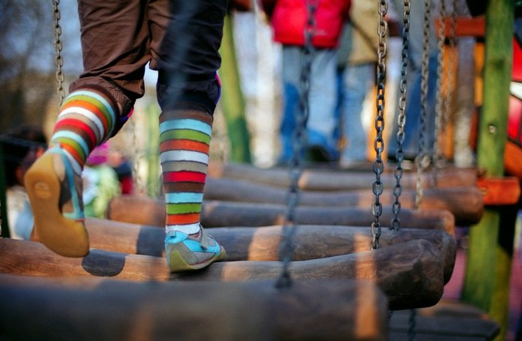 Child on a wooden bridge on a children's playground.
