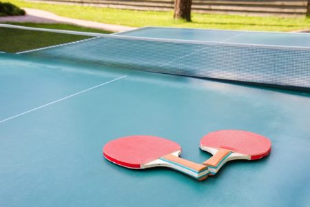 Two red table tennis ping pong racket on green board.