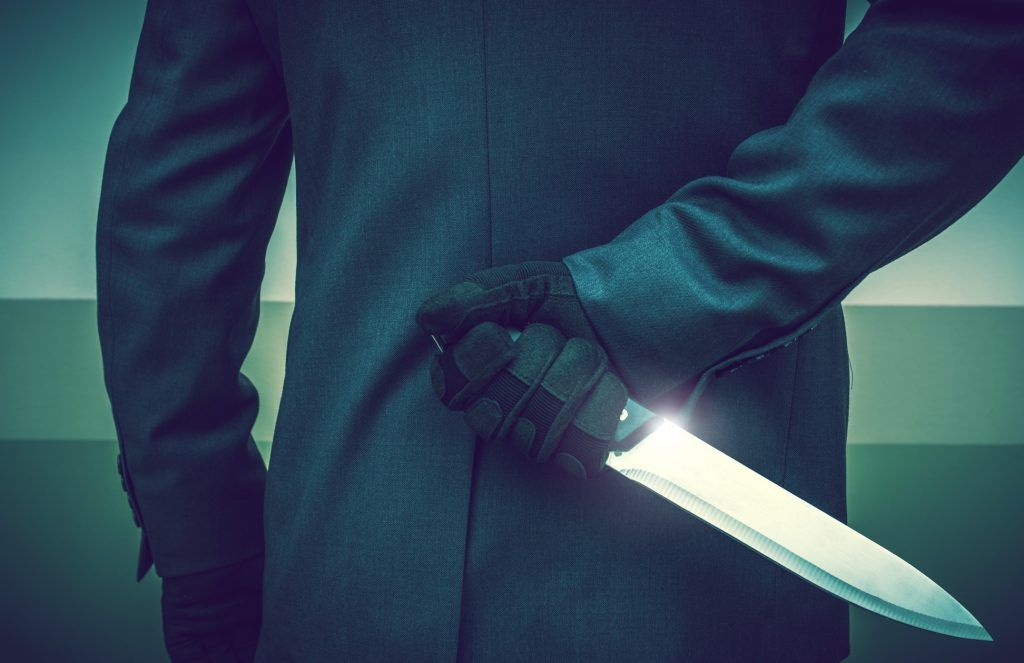 corporate boss in suit with knife behind back