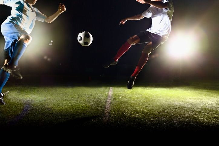 Athlete jumping towards soccer ball on field during game.