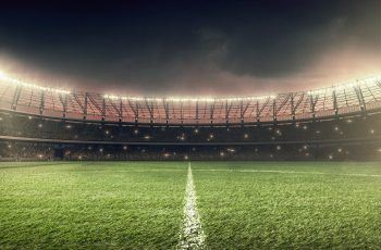 soccer stadium with illumination, green grass and dramatic night sky