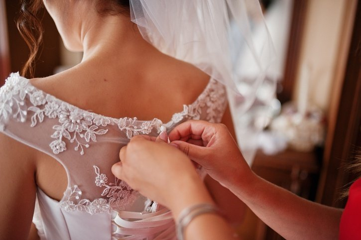 Bridesmaid helping to tie a ribbon on a wedding dress in a spacious room.