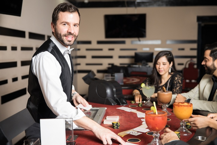 smiling casino card dealer at table