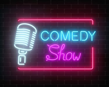 Neon comedy show sign with retro microphone on a brick wall background.