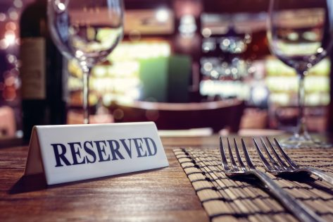 Restaurant reserved table sign with places setting and wine glasses ready for a party.