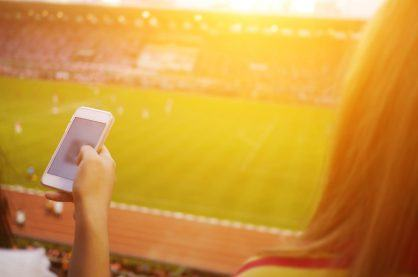 Women are using smart phone on the soccer stadium.
