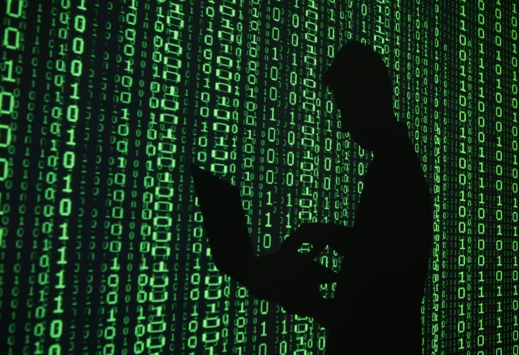 An example of a hacker, on a background of binary code
