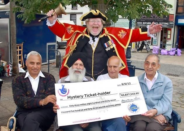 Local people posing with the largest unclaimed Euro Millions jackpot