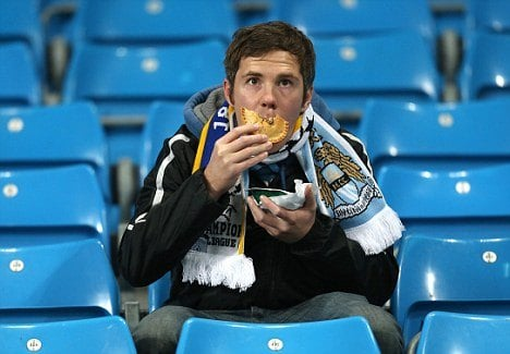 An image of a Manchester City fan eating a pie before the game