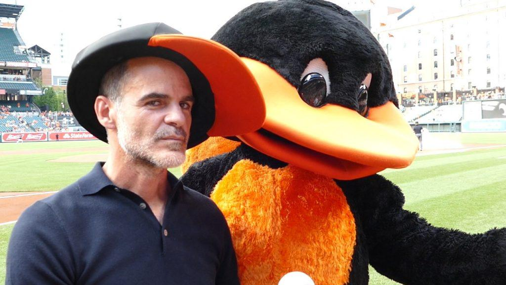 Michael Kelly posing with the Baltimore Orioles mascot