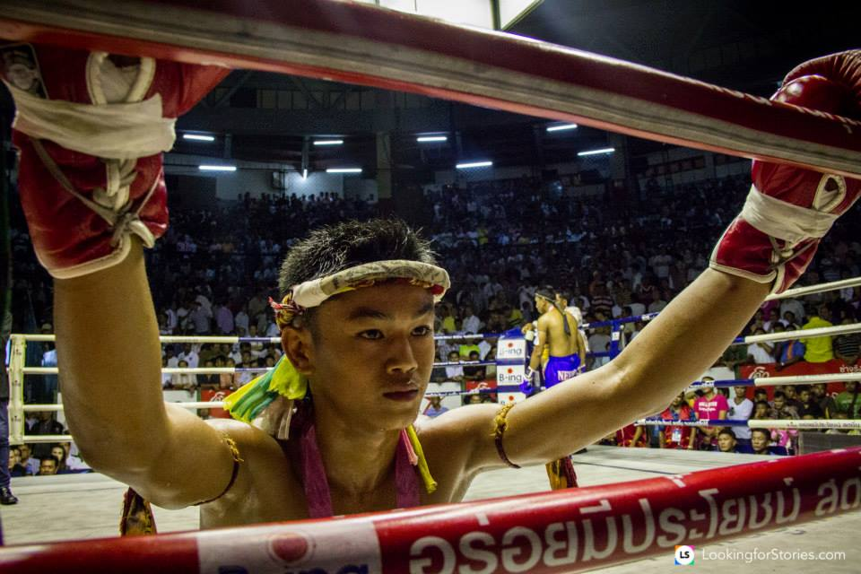 muay thai fighter on his knees looking through ropes