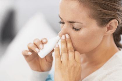 A woman using a nasal spray
