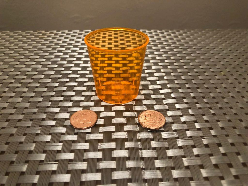 Shot glass and two coins