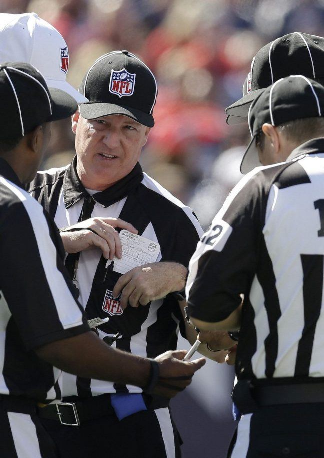 NFL referees deep in discussion during the game