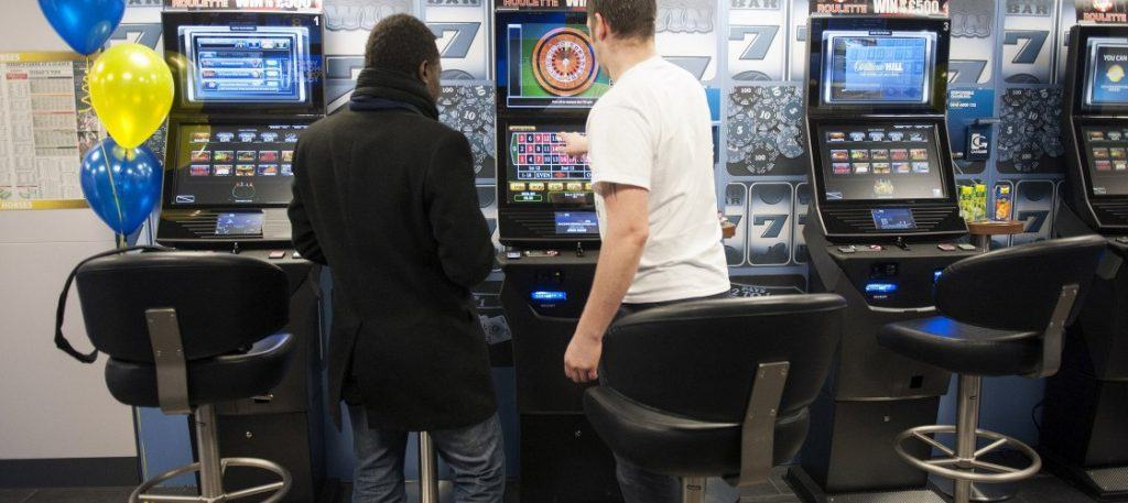 People playing the roulette machine at a bookmakers