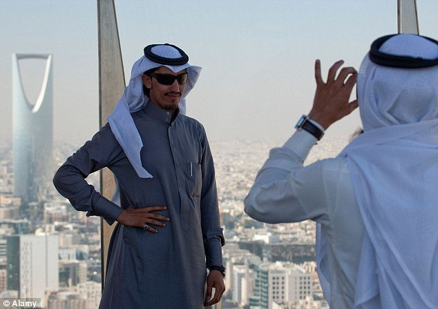 tourists in Saudi Arabia take photos at city attractions