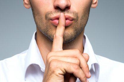 A man signalling silence, on a grey background