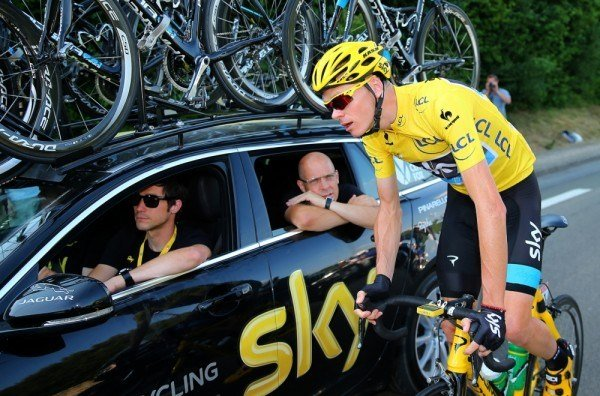 Chris Froome consulting with Team SKY during a race