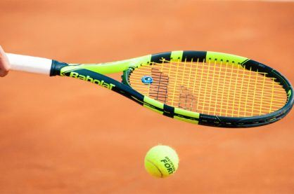 A Tennis player on a clay court surface
