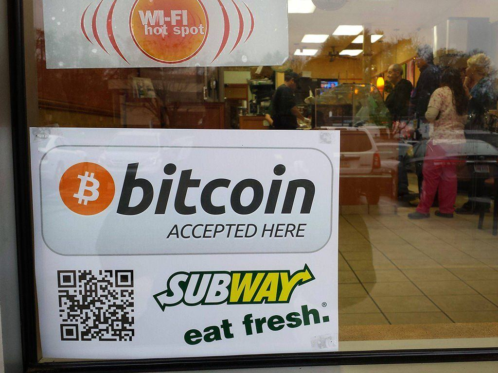 A sign promoting the use of Bitcoin in a market leading fast food store