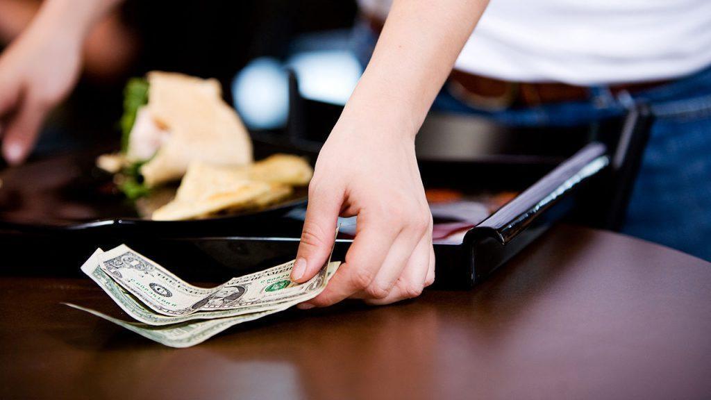 A waiter receiving a tip from a customer
