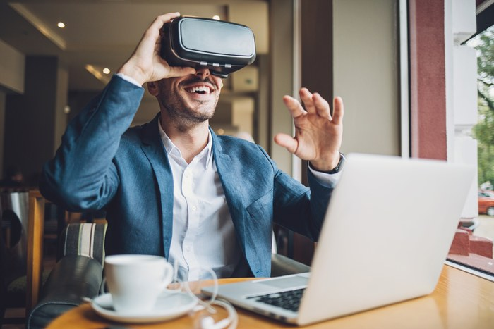 Man with virtual reality headset smiling and gesturing.