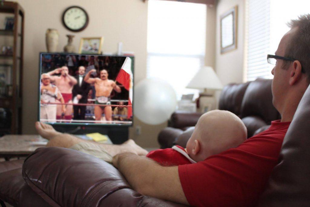 A photo of a dad and his child watching wrestling