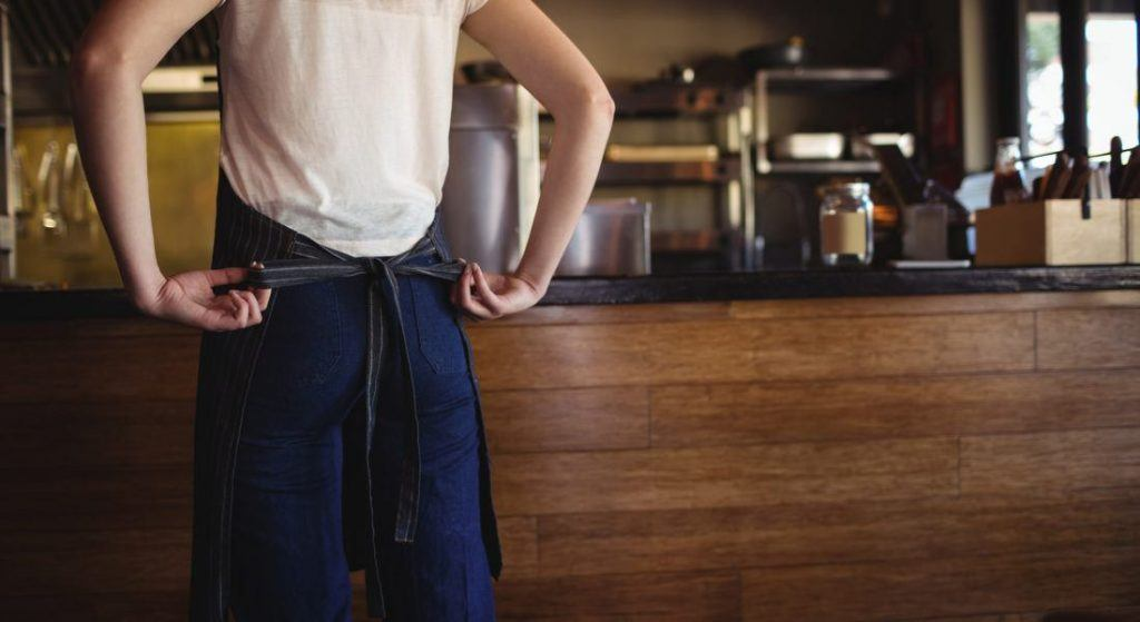 Coffee shop waitress tying on her apron