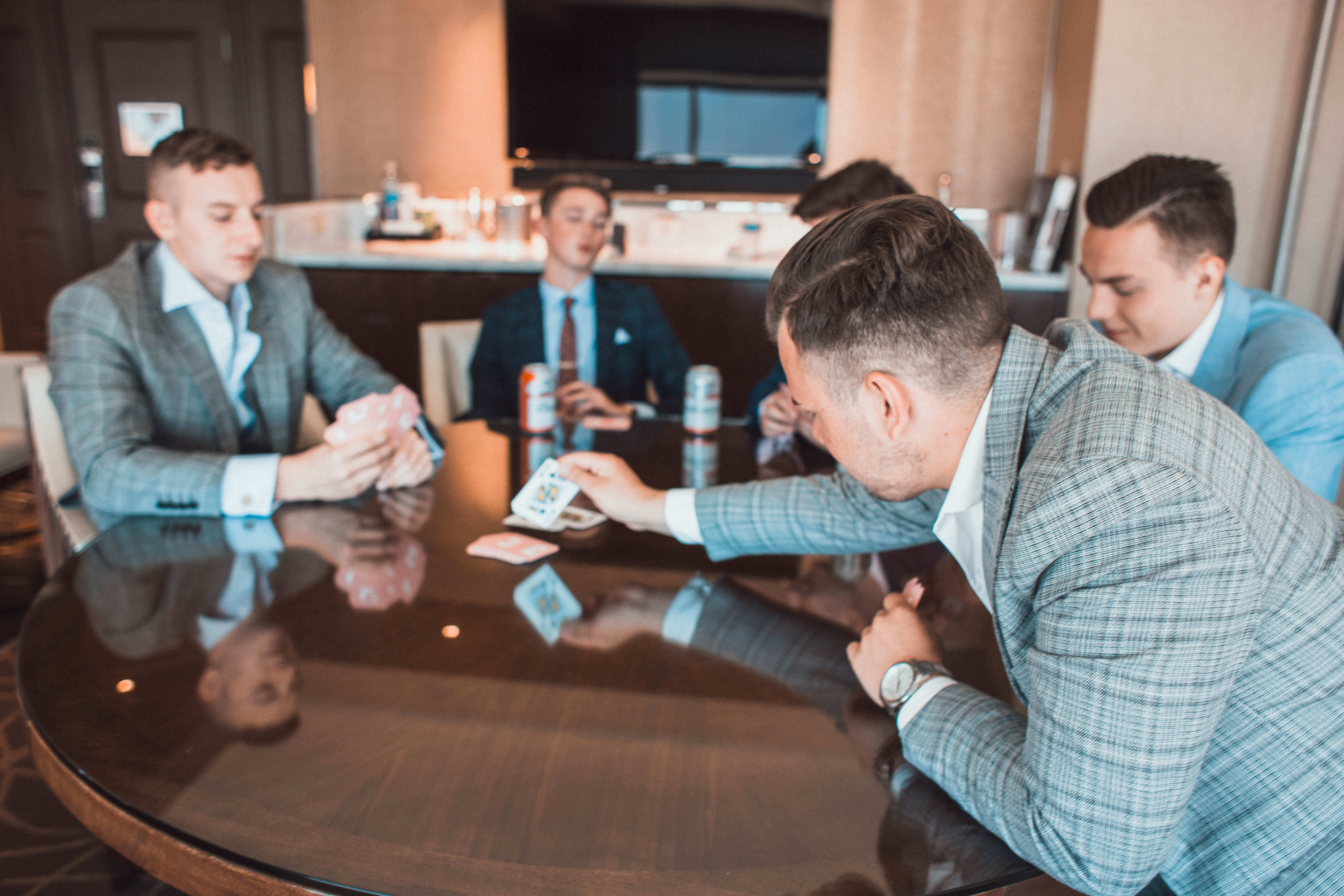 Men playing cards in gray suits.