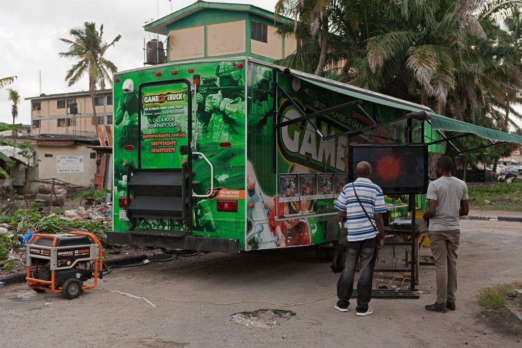 Gamers stand outside a mobile esports truck in Nigeria