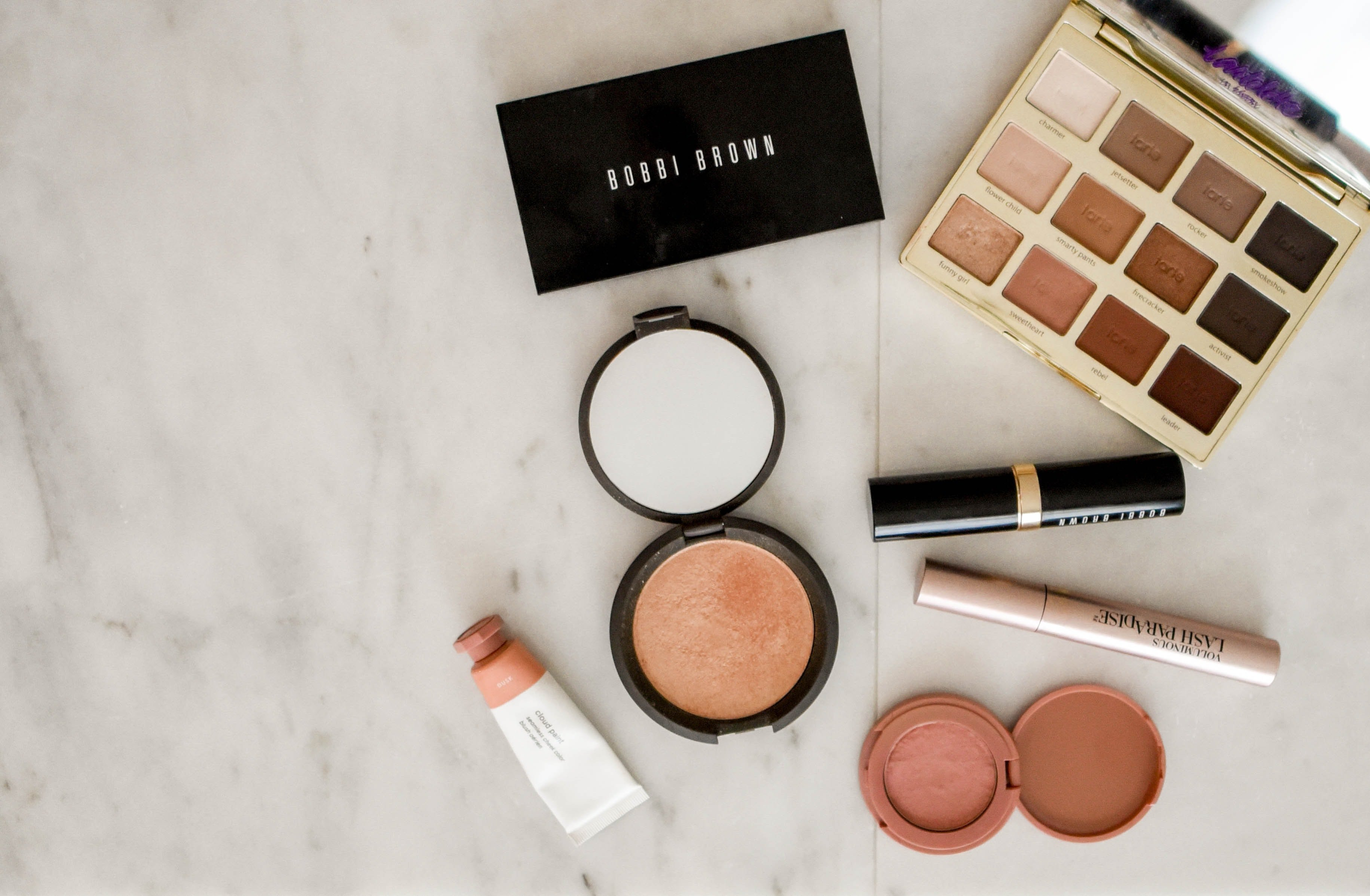 Assorted makeup products on gray surface.