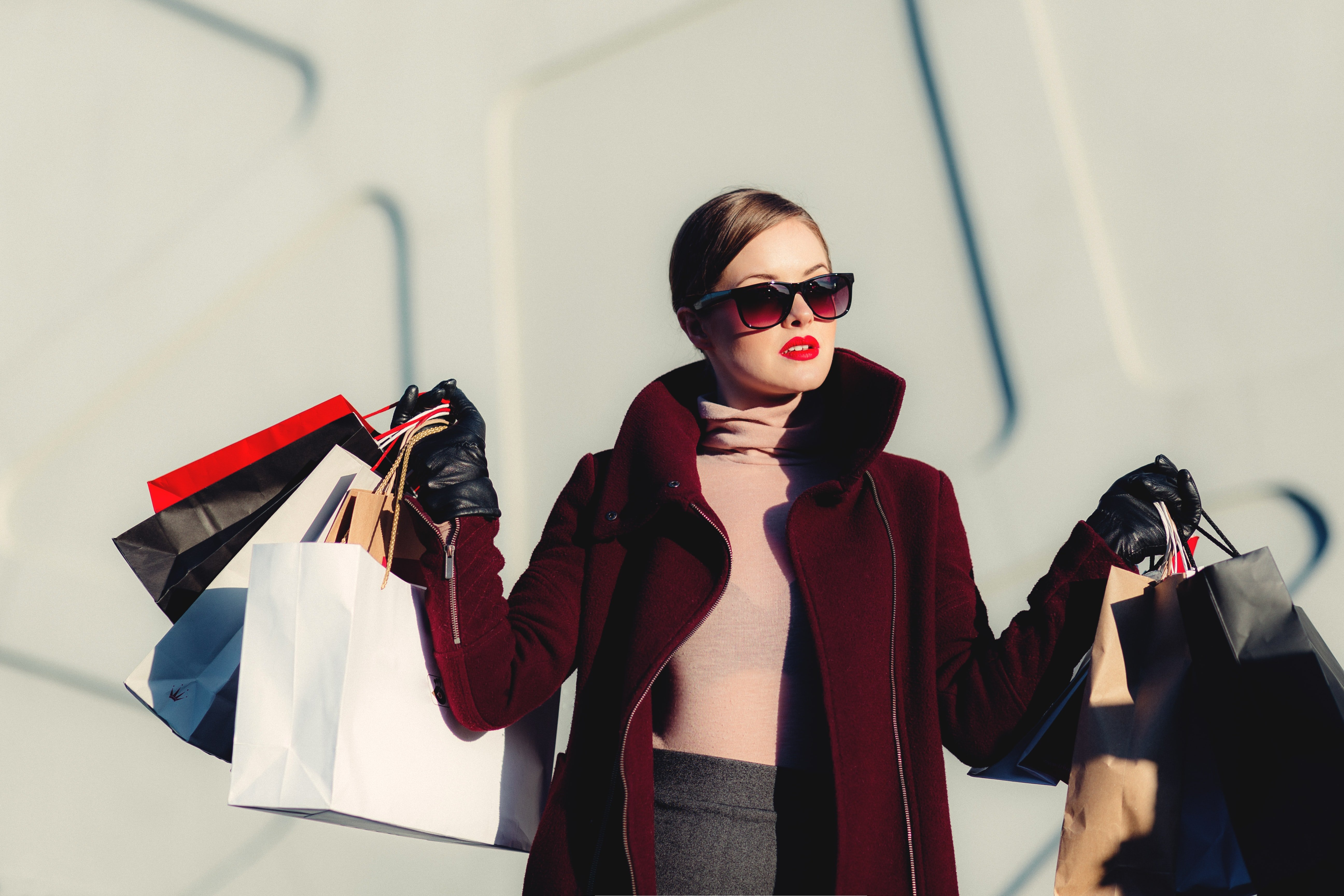 Woman holding white and black paper shopping bags.
