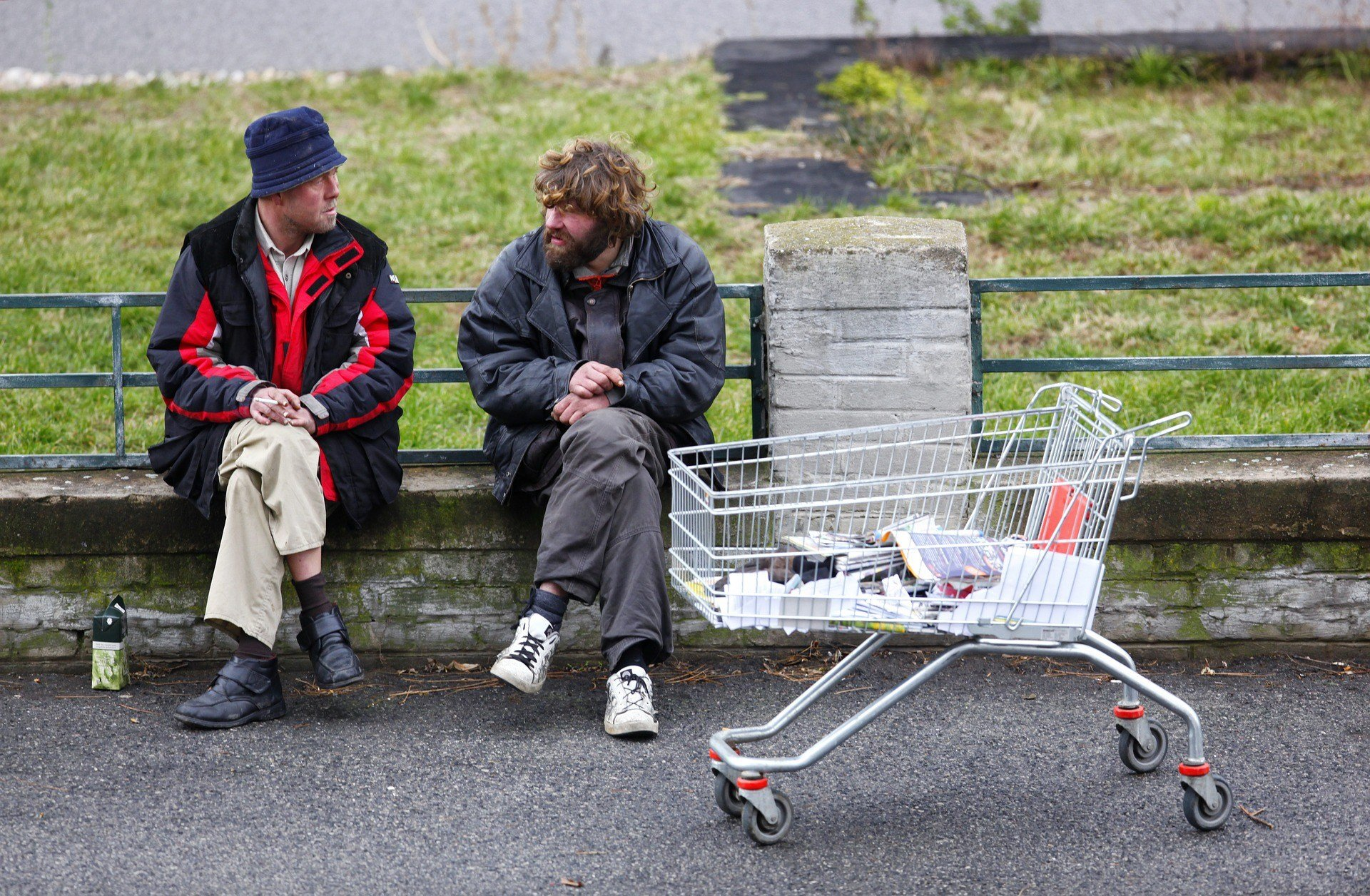 Two homeless men talking and smoking.