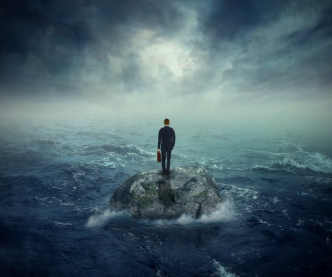 photo of lonely man standing on rock in middle of sea