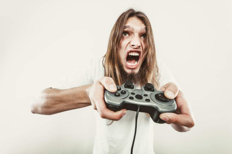man looking angry while holding game controller