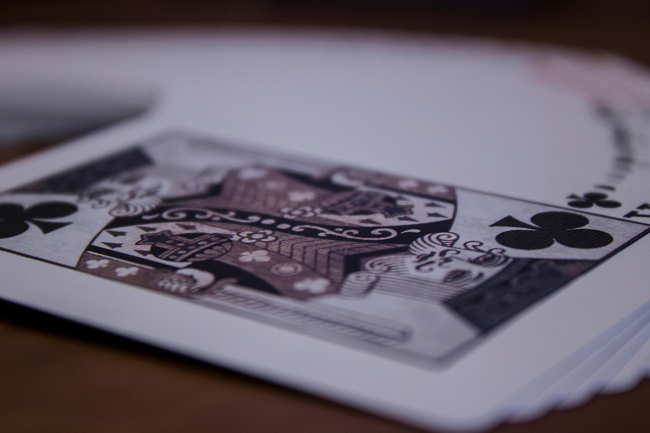 black and white photo of playing cards spread out on blackjack table