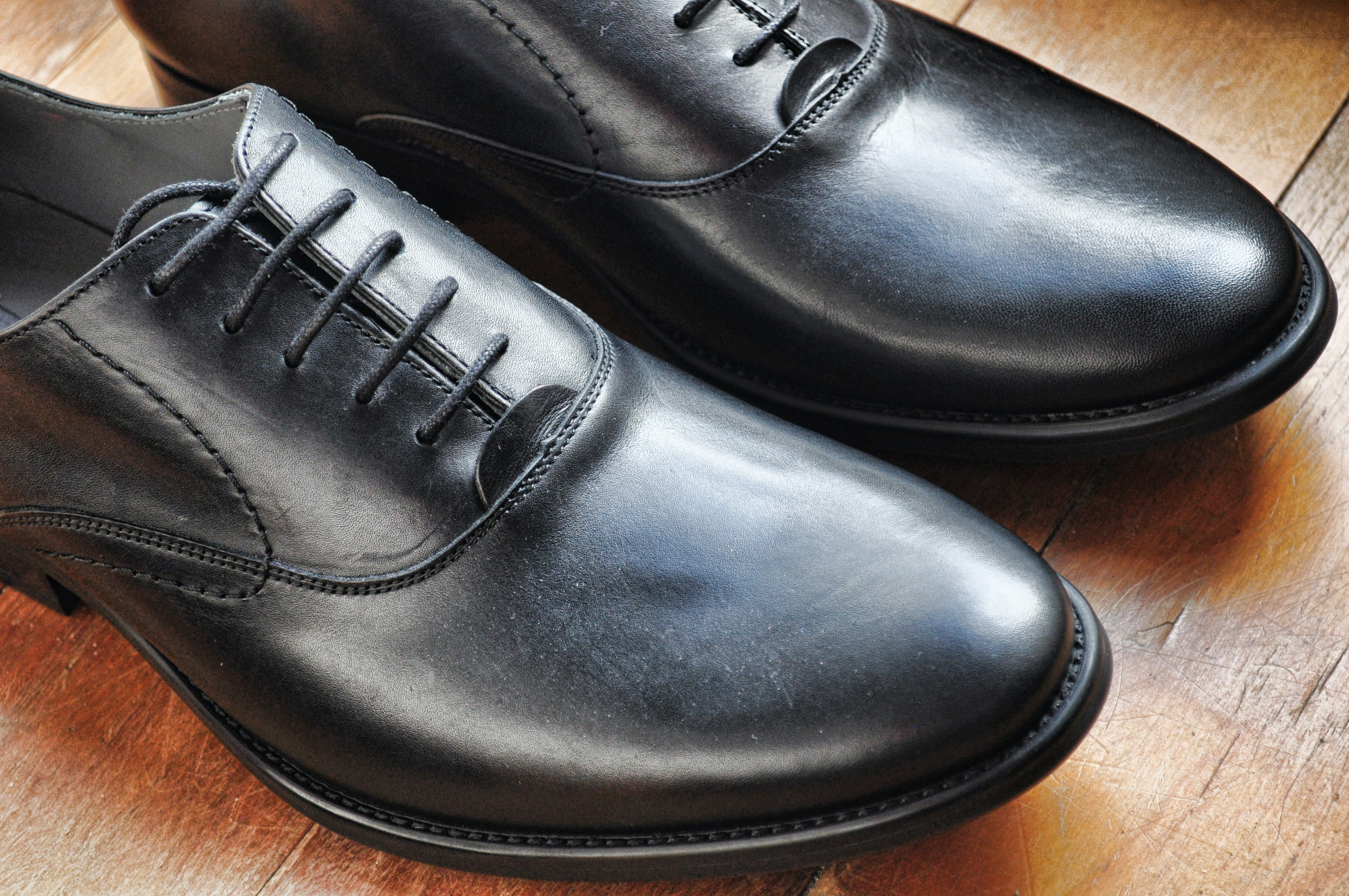 Pair of black dress shoes on top of wooden surface.