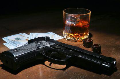 Gun with money and gambling dice