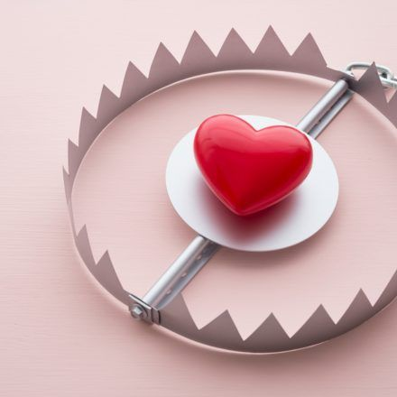 Red heart in a trap on pink background.