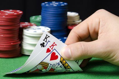 hand in foreground holding pair of kings in poker