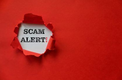 Red torn paper with a text of Scam Alert with copy space.
