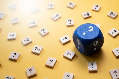 Question Mark on a dice and wooden alphabet tiles against yellow background. Concept of Choice,FAQ, Solution,Decision and luck