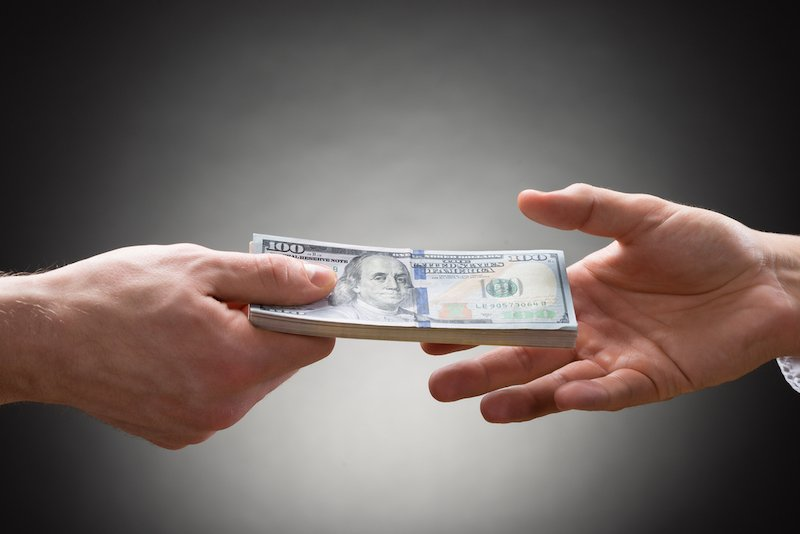 Close-up Of Person Hand Giving Money To Other Hand