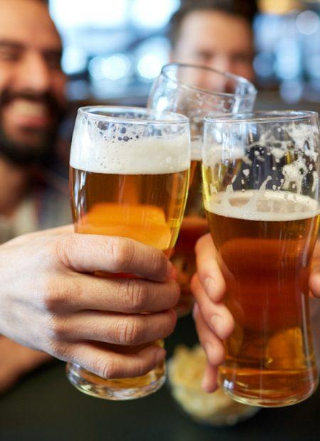 male friends drinking beer and clinking glasses at bar or pub