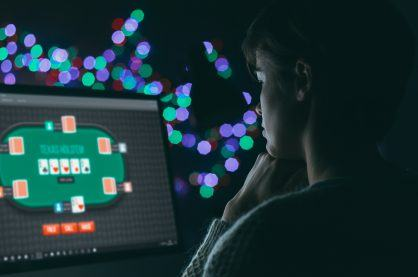 Woman playing online poker late at night