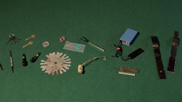 tools used to cheat at casino slot games laid out on a green background